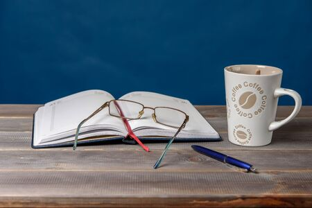 Open notebook, glasses, pencil, books and a cup of coffee on a wooden table. Preparation for classes. Archivio Fotografico