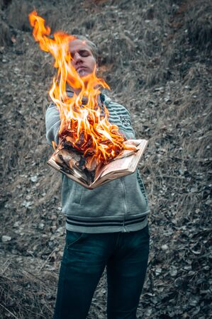 A Man Holds An Open Book In His Hands, The Pages Of Which Burn With A Bright Flame. Stock Photo