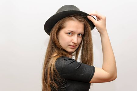 Young girl trying on a hat or straightens, on a white studio background.