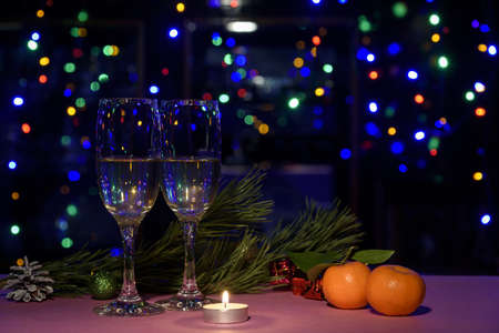 Two glasses of wine on the table. Christmas New Year lights and decorations.