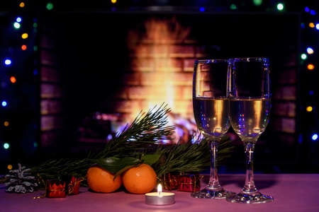 Two glasses of champagne on the table. Christmas new year lights and decorations.