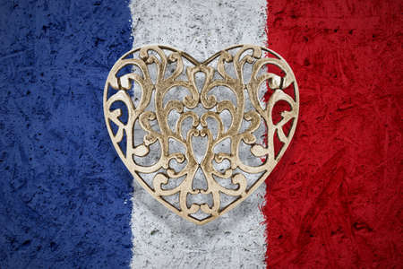 wall decor: Bronze decorative hollow heart on France flag in background Stock Photo