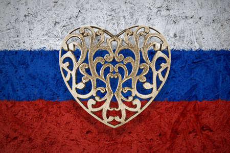 metal construction: Bronze decorative hollow heart on Russia flag in background Stock Photo