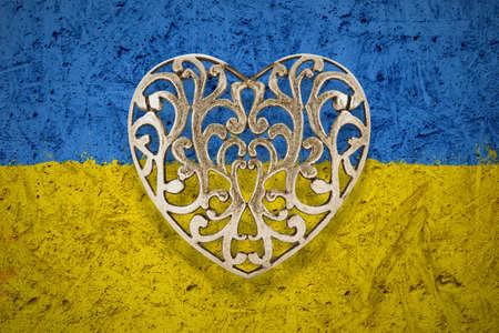 hollow: Bronze decorative hollow heart on Ukraine flag in background