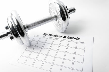 Workout schedule sheet and dumbbell on white background. photo