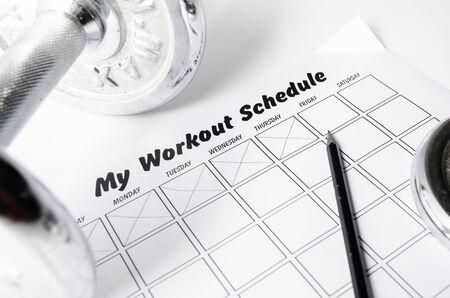 Hoja horario de entrenamiento y pesas en el fondo blanco.