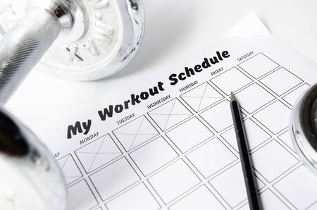Workout schedule sheet and dumbbell on white background.