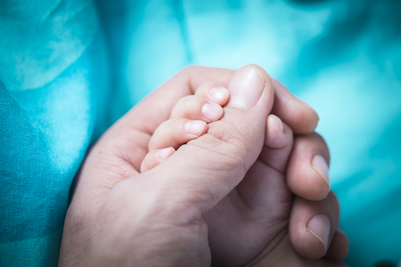 beautiful    baby: Holding Hands. hand the sleeping baby in the hand of parent close-up Stock Photo
