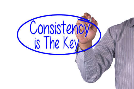 consistency: Business concept handwriting marker and write Consistency is The Key isolated on white background Stock Photo