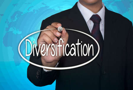 diversification: Business concept handwriting marker and write Diversification over light blue background with world map