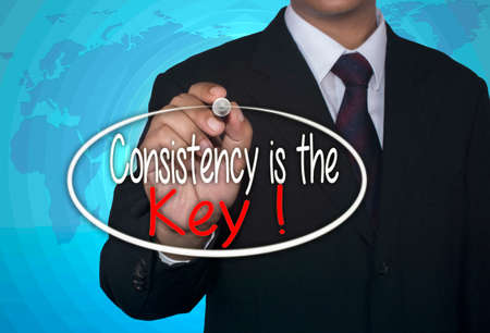consistency: Business concept handwriting marker and write Consistency is The Key over light blue background with world map