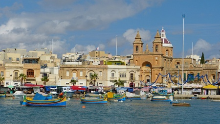 fishing fleet: Marsaxlokk, Malta - September 22, 2013. The ancient fishing village of Marsaxlokk remains resolutely a slice of real Maltese life, with old low-rise houses ringing the waterfront and a fleet of brightly coloured luzzu boats dancing in the harbour.