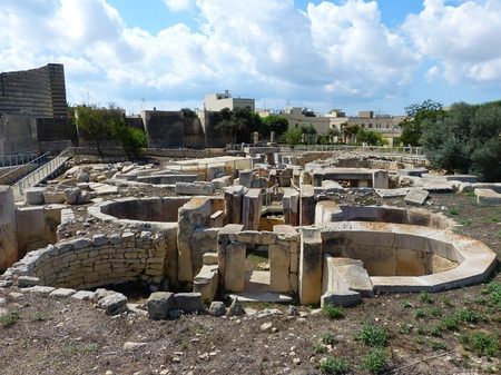 megaliths: Tarxien, Malta - September 23, 2013. Megalithic structures of the Tarxien Temples with neolithic megaliths, walkways and residential buildigs in the background.
