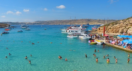 blue lagoon: Comino, Malta - 28 settembre 2013. Veduta del Blue Lagoon Comino isola di Malta, con la gente, navi da crociera e l'isola di Gozo in background. Il incredibilmente bello e invitante Blue Lagoon è la più grande attrazione di Comino. Si tratta di un co riparata Editoriali