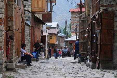 azeri: Lahic, Azerbaijan - August 30, 2014. Street view on unevenly paved Huseynov street, the main street of Lahic mountainous village of Azerbaijan, with smooth pale river stones, coppersmith workshops and people. Houses with wooden box balconies are built tra Editorial