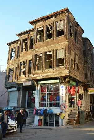 constantinople ancient: Istanbul, Turkey - November 4, 2015. Old Ottoman house in Istanbul, with commercial properties on the ground floor and people.
