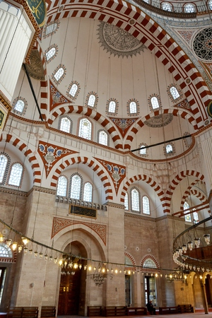 mehmet: Istanbul, Turkey - November 5, 2015. Interior of Shehzade Mehmet mosque in Istanbul, with ornamental semi-dome ceiling and walls, Arabic inscriptions, lamps and people. It was the first important mosque to be designed by Mimar Sinan. Editorial