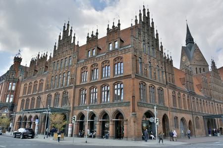 Hanover, Germany - April 18, 2016. Altes Rathaus building on Karmarschstr street in Hanover, with commercial properties, cars, people and spire of Marktkirche in the background.