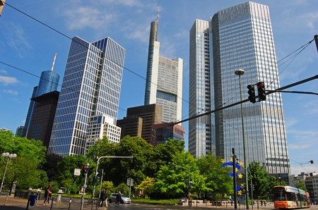 Frankfurt-on-Main, Germany - May 9, 2014. View of Financial district in Frankfurt,with commercial buildings, including Commerzbank Tower, Eurotower, Bank of America tower and Taunusturm, with tram and people.