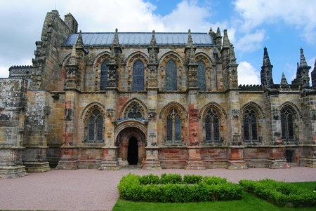 Roslin, Great Britain - June 18, 2014. Exterior view of Rosslyn Chapel, with grass lawn, on cloudy summer day.