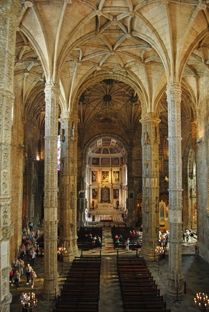 baukunst: Lisbon, Portugal - October 21, 2014. Interior of the church of Mosteiro dos Jeronimos in Lisbon, with view toward the Main Altar, columns, benches and people.