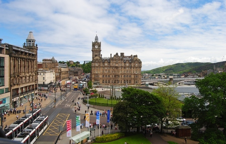 giles: Edinburg, Great Britain - June 14, 2014. View down Princes St in Edinburg, with historic building, including Balmoral Hotel, street traffic, people and vegetation. Editorial
