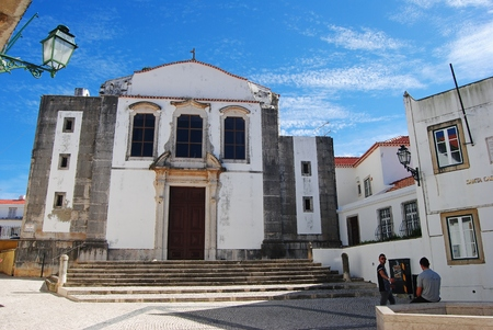 Cascais, Portugal - October 23, 2014. Church of Igreja da Misericordia in Cascais, with surrounding buildings, street lamp and people.