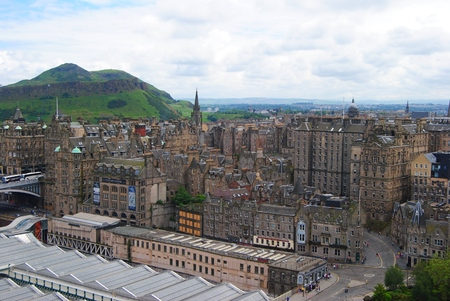 the crags: Edinburg, Great Britain - June 14, 2014. View over Edinburgh towards Salisbury Crags, with historic buildings, Arthurs Seat and people. Editorial