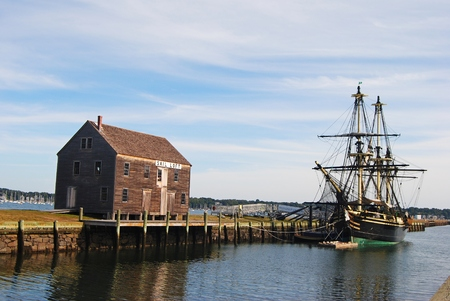 Salem, Massachusetts, USA - September 25, 2014. The wharves are among remnants of the shipping industry that once thrived in Salem, MA. View with historic ship,pier and timber building.