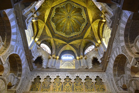 incorporates: Cordoba, Spain - July 18, 2015. Ornate ceiling above the mihrab in the Mezquita of Cordoba, with paintings and inscriptions. The entire mihrab portal incorporates 1600kg of gold mosaic cubes, a gift from the Christian emperor of Byzantium.