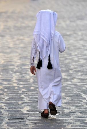 thobe: Figure of unidentifiable Arabic boy in white thobe walking away in Doha, Qatar. Stock Photo