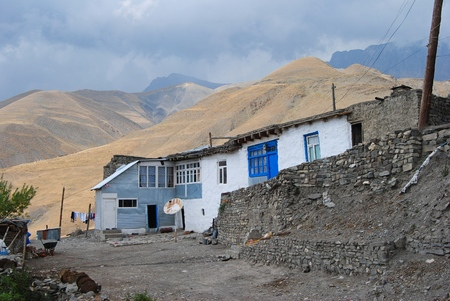 azeri: Xinaliq, Azerbaijan - August 23, 2014. Residential house in Xinaliq village, with linen put out to dry, satellite antenna and mountains in the background.