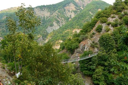 Lahic, Azerbaiyán - 11 de agosto de 2017. Pasarela de suspensión Zarnava a través del río Girdimancay cerca de Lahic, con personas. Editorial