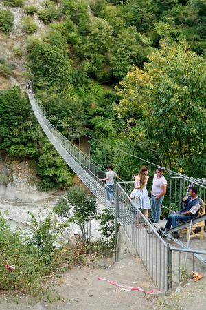 Lahic, Azerbaiyán - 11 de agosto de 2017. Pasarela de suspensión Zarnava a través del río Girdimancay cerca de Lahic, con personas.