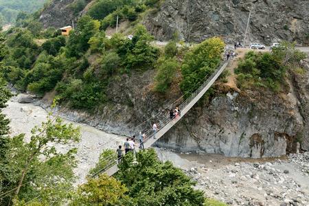 """Lahic, Azerbaiyán â ? """"11 de agosto de 2017. Pasarela de suspensión Zarnava a través del río Girdimancay cerca de Lahic, con personas y automóviles. Editorial"""