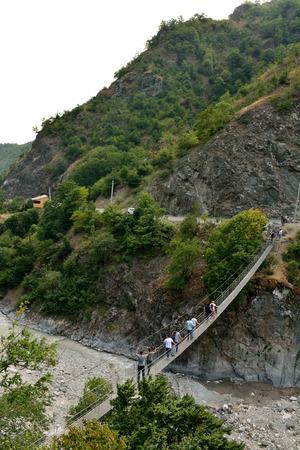 """Lahic, Azerbaiyán â ? """"11 de agosto de 2017. Pasarela de suspensión Zarnava a través del río Girdimancay cerca de Lahic, con personas y automóviles."""