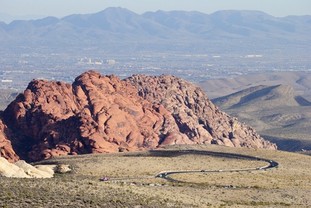 Steep, rugged red-rock escarpment of Red Rock Canyon rising in Nevada, USA, with scenic loop drive road.