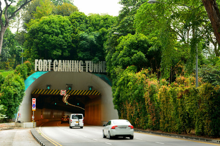 Singapore, Singapore - December 11, 2017. Entrance to the Fort Canning tunnel in Singapore, with cars and vegetation.