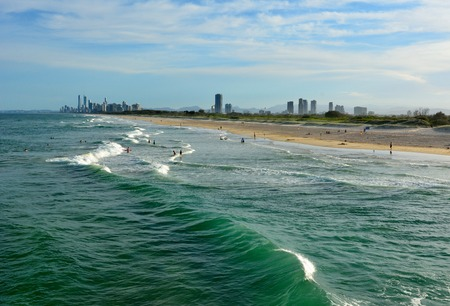 Beach at the Spit, with people and skyscrapers of Surfers Paradise in the distance.