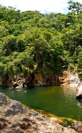 View of swimming hole at Wheel of Fire falls in Eungella National Park in Queensland, Australia, with unidentifiable figures of people.