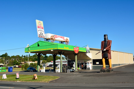 Maryborough, Queensland, Australia - December 20, 2017. Gas station in Maryborough, QLD, with oversized statue of outlaw Ned Kelly, commercial properties and cars. Sajtókép