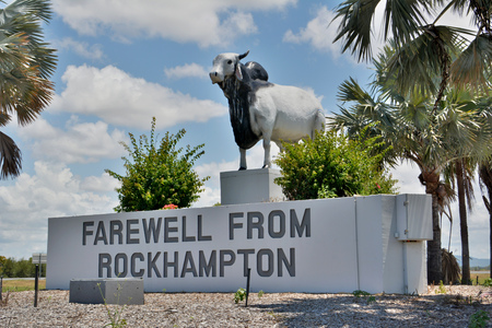 Rockhampton, Queensland, Australia - December 28, 2017. Statue of Brahman bull, at the Yeppen roundabout at Fairy Bower, the junction of the Bruce Highway and Capricorn Highway, with Farewell from Rockhampton sign.