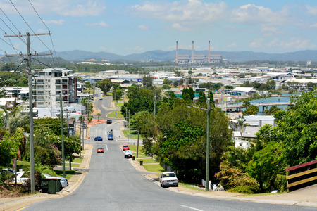 Gladstone, Queensland, Australia - January 3, 2018. View down a steep street in a hilly neighbourhood of Gladstone, toward the Powerhouse, with buildings, electricity poles and cars.