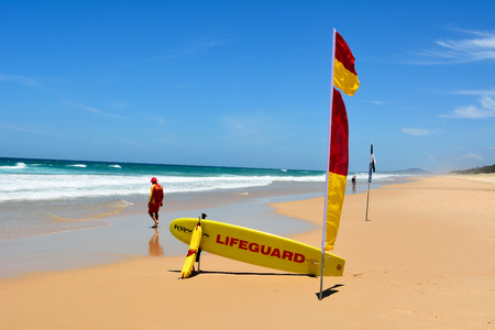 Noosa, Queensland, Australia - December 20, 2017. Surf lifesaver near red-yellow flag and rescue board at Sunshine Beach south of Noosa, QLD. Editöryel