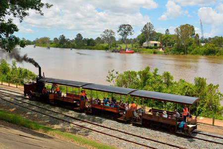 Maryborough, Queensland, Australia - December 21, 2017. Mary Ann steam locomotive riding through Queens Park in Maryborough, QLD, with people and Mary River in the background. Editöryel