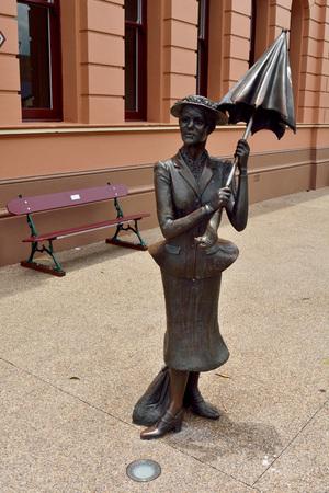 Maryborough, Queensland, Australia - December 21, 2017. Life-size bronze statue of umbrella-wielding Mary Poppins on the corner of Richmond and Wharf streets in Maryborough, QLD. Editöryel