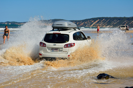 Rainbow Beach, Queensland, Australia - December 23, 2017. 4WD Hyundai car driving across a washout in splashes of ocean water on Rainbow Beach in Queensland, Australia.