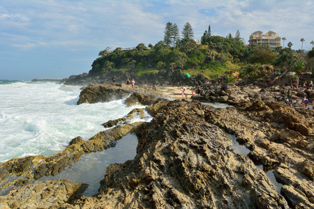 Tweed Heads, Gold Coast, Queensland, Australia - January 13, 2018. Rocky coastline at Point Danger headland on the Gold Coast of Queensland, with people.