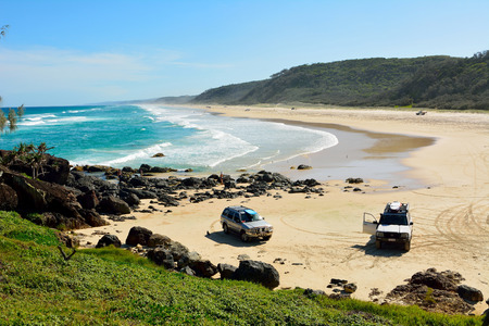 Great Sandy National Park, Queensland, Australia – December 19, 2017. 40-mile beach in Great Sandy National Park in Queensland, Australia, with 4WD Nissan and Toyota cars parked on sand, and people. Editöryel