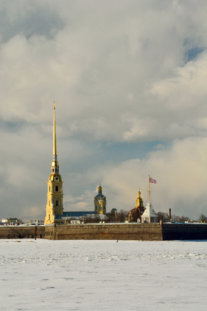 Exterior view of Peter and Paul Fortress and Cathedral in St Petersburg, Russia, across frozen Neva River.